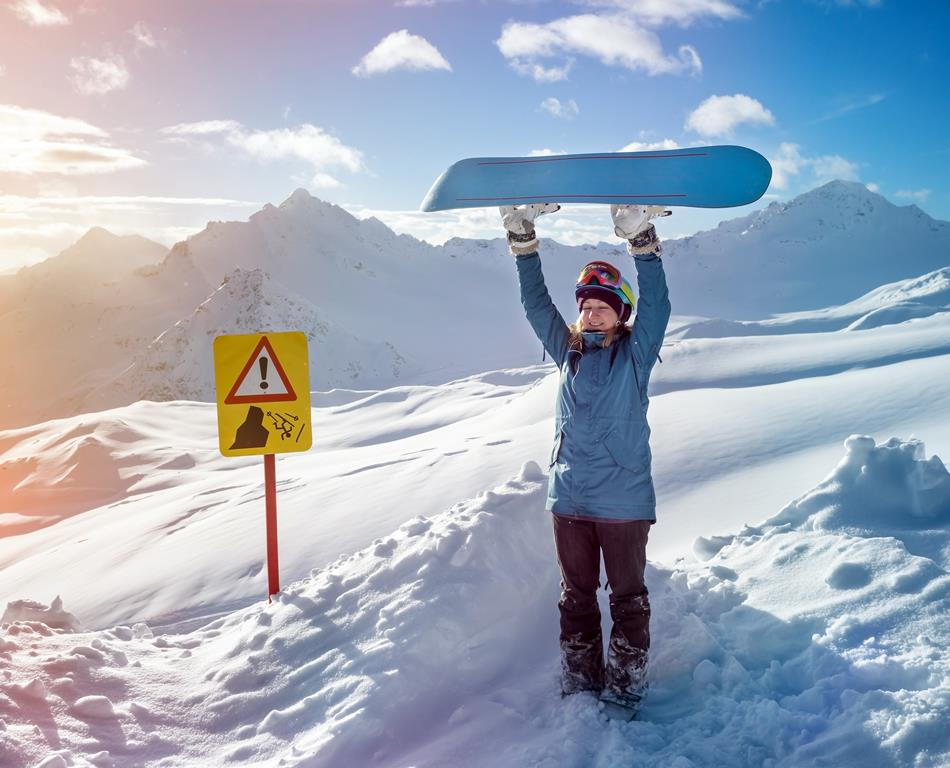 Portrait of snowboarder woman on background beautiful landscape of snowy high mountains Elbrus standing with raised up snowboarding