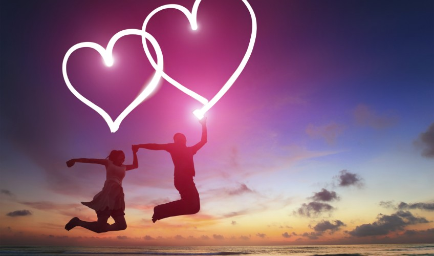 silhouette of young couple jumping and drawing love heart by digital tablet pc flashlight in the air on the beach
