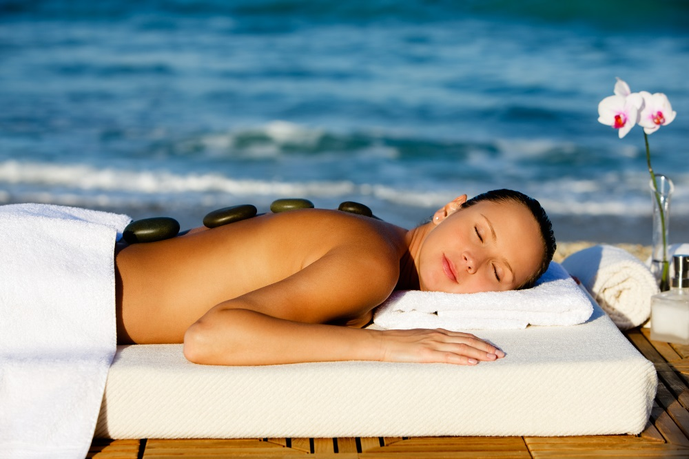 woman at the beach on a wooden deck getting spa stone massage